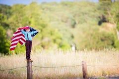 拿着一面大美国国旗的一个年轻男孩 免版税库存照片