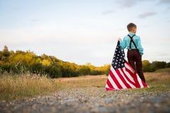 拿着一面大美国国旗,美国独立日的一个年轻男孩 免版税库存图片