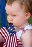 拿着一面美国国旗和乘坐在红色无盖货车的女孩获得乐趣在7月四的公园 免版税图库摄影