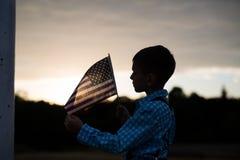 拿着一面美国国旗的剪影年轻男孩的 免版税库存照片