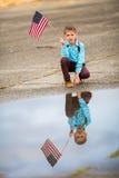 拿着一面美国国旗,喜悦的一个年轻男孩是美国人 免版税库存照片