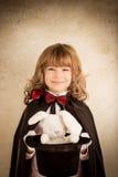 拿着一顶高顶丝质礼帽用玩具兔子的魔术师 免版税库存照片