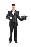 拿着一顶魔术鞭子和高顶丝质礼帽的魔术师 图库摄影