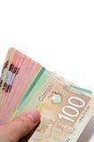 拿着一系列的加拿大钞票的手 免版税库存照片