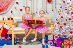 拿着一件大红色礼物的愉快的姐妹和坐在圣诞节设置的一条长凳 库存照片