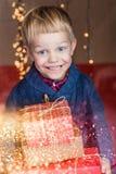 拿着一件新的礼物的一个愉快的小男孩的画象 圣诞节 生日 免版税库存照片
