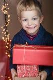拿着一件新的礼物的一个愉快的小男孩的画象 圣诞节 生日 免版税库存图片
