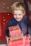 拿着一件新的礼物的一个愉快的小男孩的画象 圣诞节 生日 免版税图库摄影
