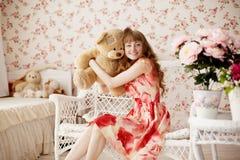拿着一头玩具熊的妇女在托儿所 免版税图库摄影