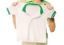 拿着一件白色干净的衬衣的手。 免版税库存图片