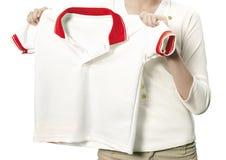 拿着一件白色干净的衬衣的手。 库存图片