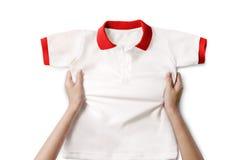 拿着一件白色干净的衬衣的手 免版税库存照片