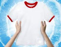 拿着一件白色干净的衬衣的手 免版税库存图片