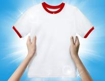拿着一件白色干净的衬衣的手 库存照片
