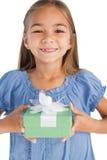 拿着一件被包裹的礼物的快乐的小女孩 免版税库存图片