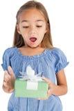 拿着一件被包裹的礼物的惊奇的小女孩 免版税库存照片