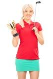 拿着一件金黄战利品的女性高尔夫球运动员 免版税图库摄影