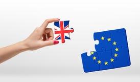 拿着七巧板的片断与欧盟和大英国旗子的妇女的手在白色背景 免版税库存图片