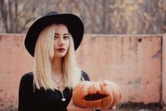 拿着万圣节南瓜的黑色大衣的年轻女人有从里边来它的白色烟的在秋天 免版税图库摄影