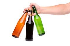 拿着三啤酒瓶的人的手 免版税库存照片
