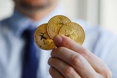 拿着三枚Bitcoin硬币的人手中 免版税图库摄影