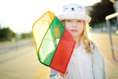 拿着三色立陶宛旗子的逗人喜爱的女孩在立陶宛国家地位天 库存照片
