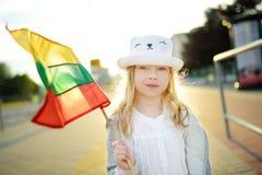 拿着三色立陶宛旗子的逗人喜爱的女孩在立陶宛国家地位天 免版税库存照片