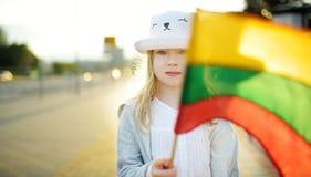 拿着三色立陶宛旗子的逗人喜爱的女孩在立陶宛国家地位天 库存图片