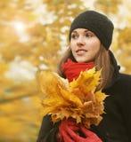 拿着下落的叶子的一个少妇的画象 库存照片