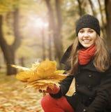 拿着下落的叶子的一个少妇的画象 免版税库存图片