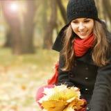 拿着下落的叶子的一个少妇的画象 图库摄影