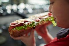 拿着不健康的食物的肥胖妇女 图库摄影