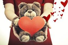 拿着不可思议的心脏和软的玩具的女性手 免版税库存图片