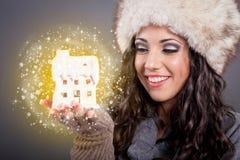 拿着不可思议的房子,圣诞节的白色帽子的美丽的少妇 免版税图库摄影