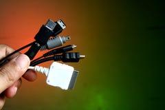 拿着不同的小配件充电器的手 免版税库存图片