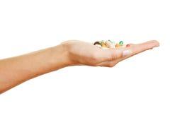 拿着不同的药物的手 库存图片