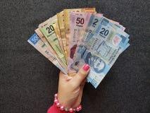 拿着不同的衡量单位的墨西哥钞票妇女的手 免版税库存图片