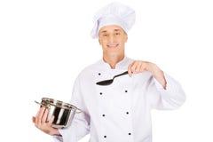 拿着不锈钢罐和匙子的厨师 库存图片