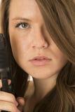 拿着与一个严肃的表示的年轻女性一把大左轮手枪 免版税图库摄影