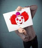 拿着与一个小丑的商人纸板对此在他的头前面 库存图片