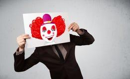 拿着与一个小丑的商人纸板对此在h前面 库存照片
