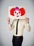 拿着与一个小丑的商人纸板对此在h前面 库存图片