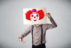 拿着与一个小丑的商人纸板对此在h前面 免版税库存图片
