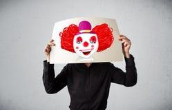 拿着与一个小丑的商人纸板对此在h前面 图库摄影