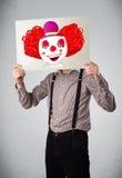拿着与一个小丑的商人纸板对此在h前面 免版税图库摄影