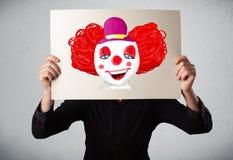 拿着与一个小丑的商人纸板对此在h前面 免版税库存照片