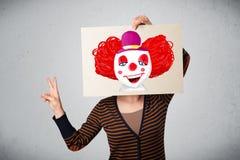 拿着与一个小丑的妇女纸板对此在她的hea前面 库存照片
