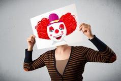 拿着与一个小丑的妇女纸板对此在她的hea前面 免版税库存图片