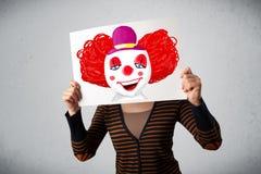拿着与一个小丑的妇女纸板对此在她的hea前面 图库摄影