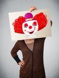 拿着与一个小丑的妇女纸板对此在她的hea前面 库存图片